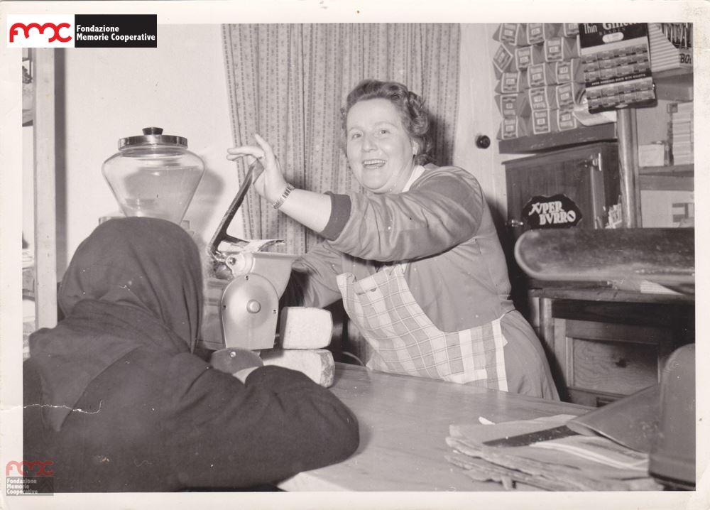 Foto 5. Primo piano di una dipendente di uno spaccio cooperativo, fine  anni '50