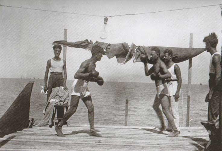 Fig. 6. La piattaforma di uno chalet diventa il ring per un incontro di box sulla spiaggia, sopra una lampadina, anni '20-40, in Perfetti, Carlorosi, Buschi 2007, 180.