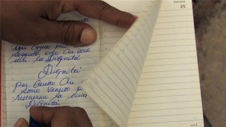 Foto1 Zakaria Mohamed Ali, Scrittura sul molo di Lampedusa per il corto To whom it may concern, Lampedusa 2012 (©Zakaria Mohamed Ali)