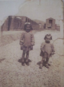 Foto 2. Due giovanissime profughe appena giunte a Fertilia nel 1949 (sullo sfondo si noti la desolazione dell'abitato), in Ame.